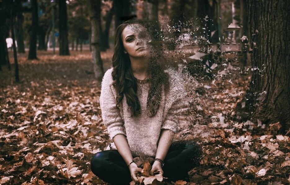 На фото грустная девушка в осеннем лесу.