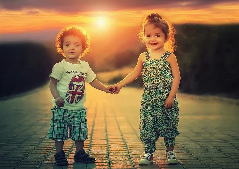 Мальчик и девочка держатся за руку. Фото на фоне заката.