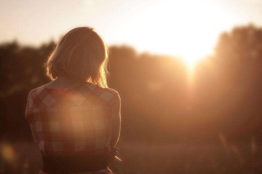 Девушка мечтает на фоне заката.