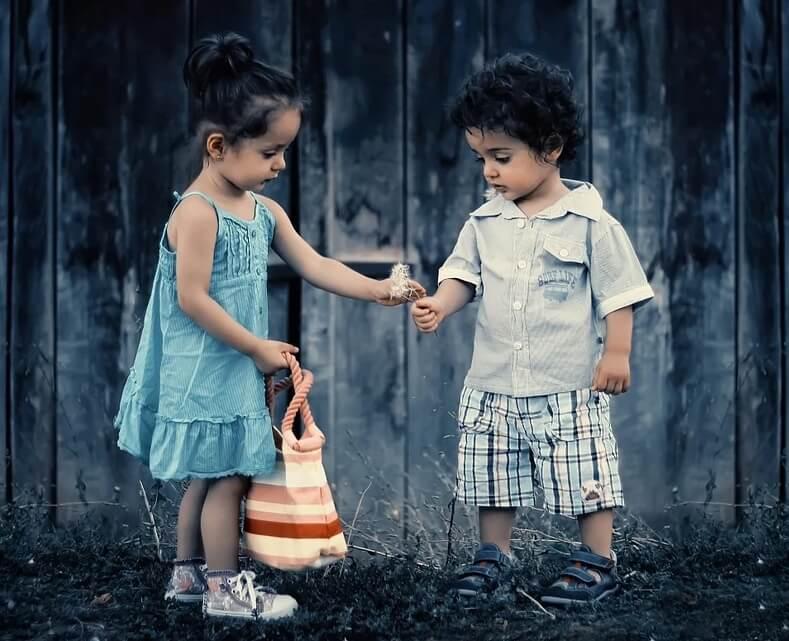 На фото мальчик и девочка с одуванчиками.