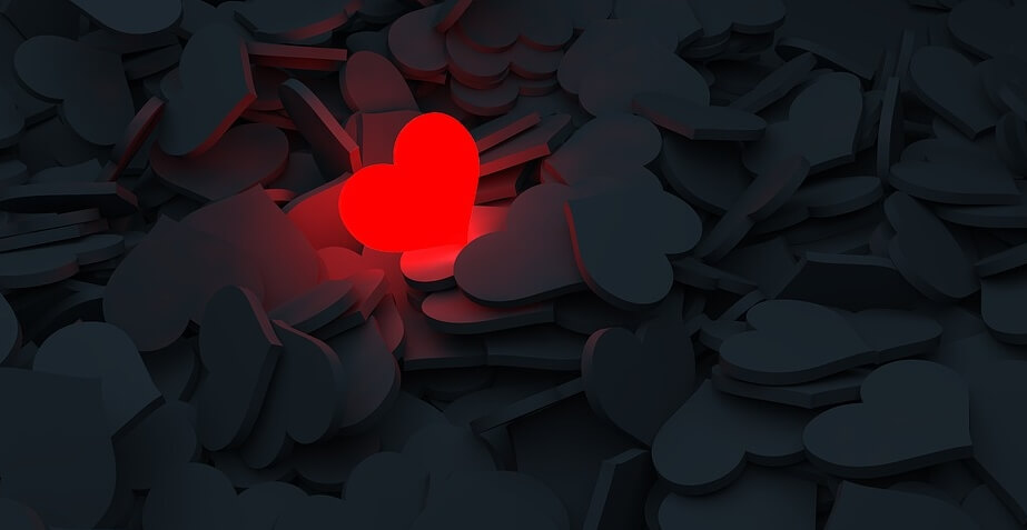 На фото изображено куча сердец, и одно среди них горит красным.