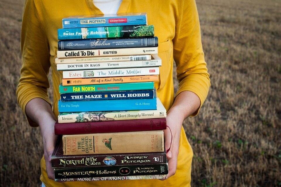На фото изображена стопка книг в руках у девушки.