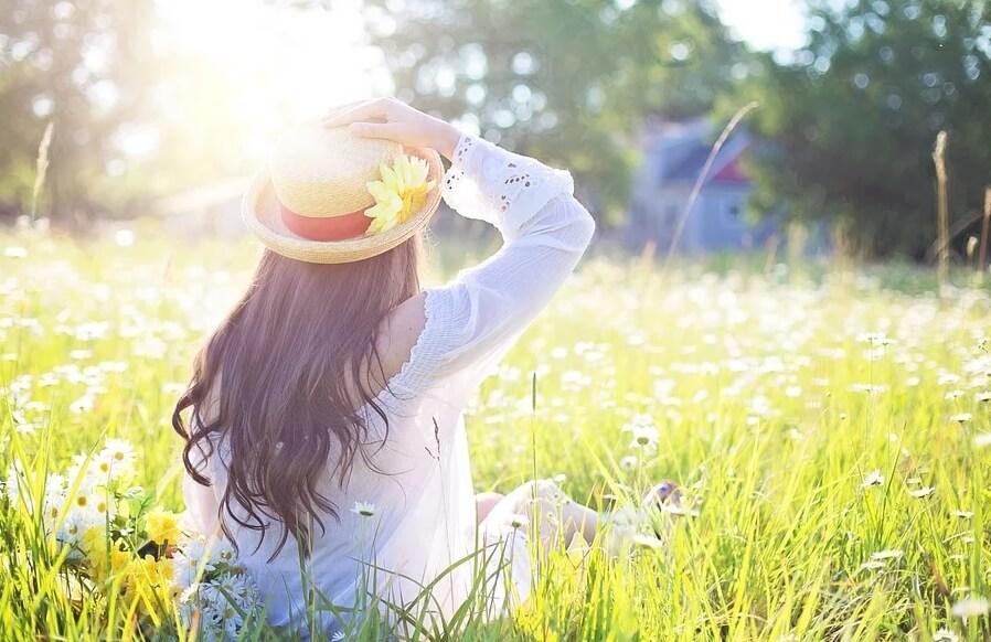 На фото девушка, сидящая в траве на солнце.