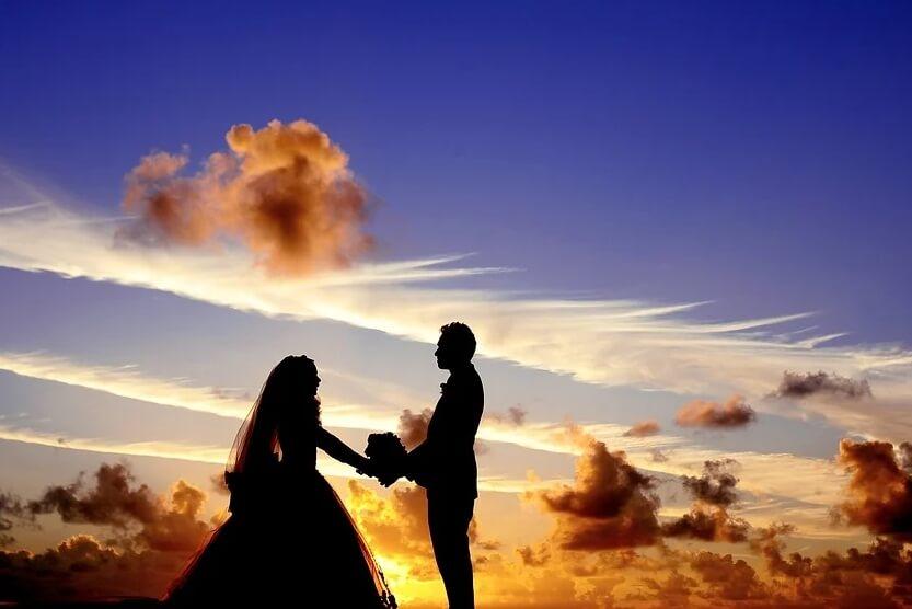 На фото изображена молодая пара в свадебных нарядах на фоне заката.