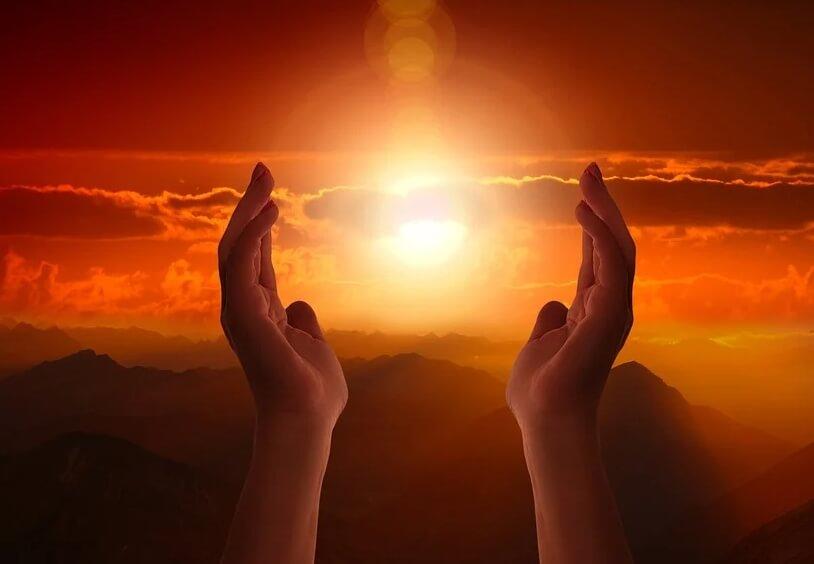 На фото изображены руки, которые словно держат закат.