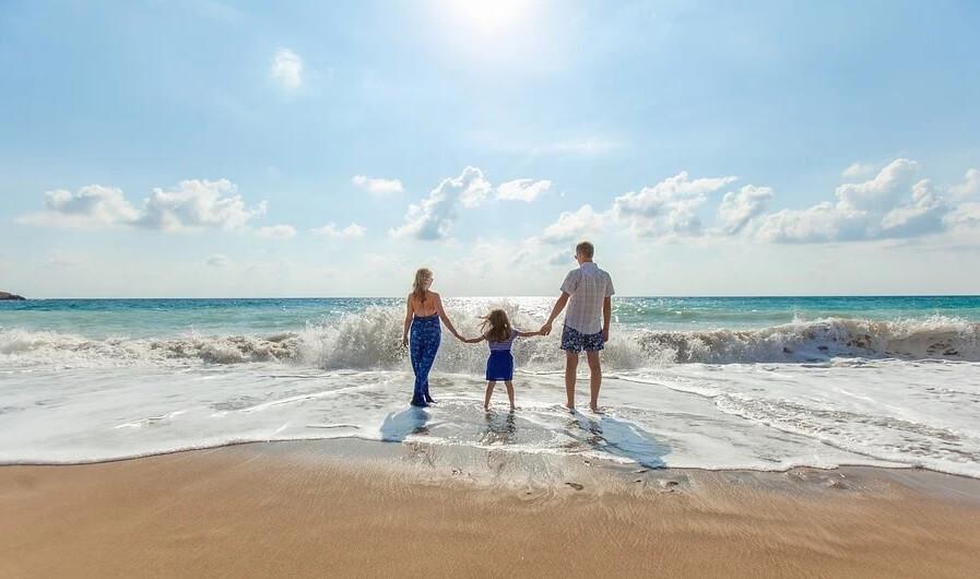 На фото семья с ребенком на море.