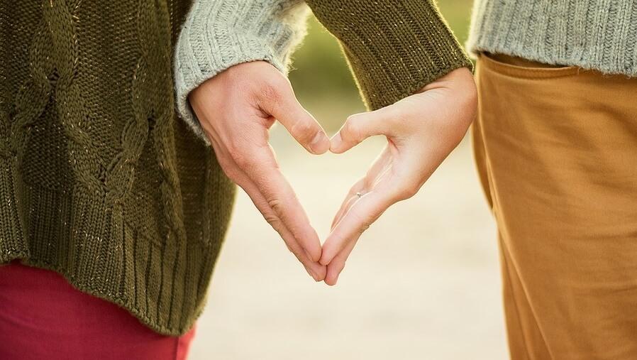 На фото влюбленная пара, держащаяся за руки.