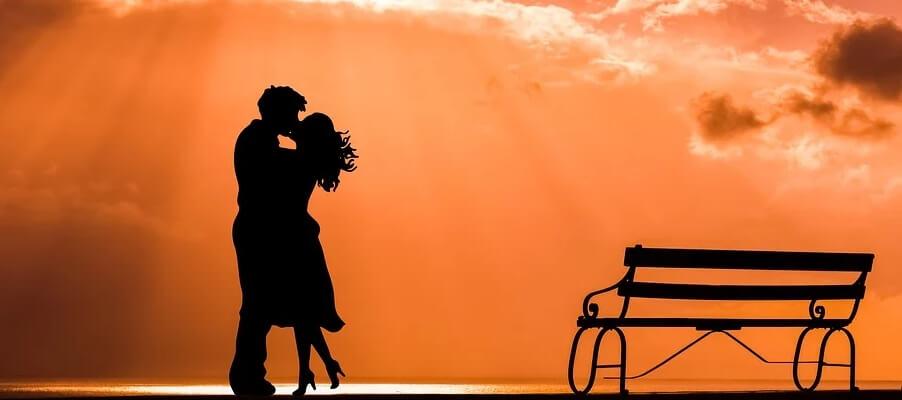 На фото молодая пара возле лавочки. Целуются.