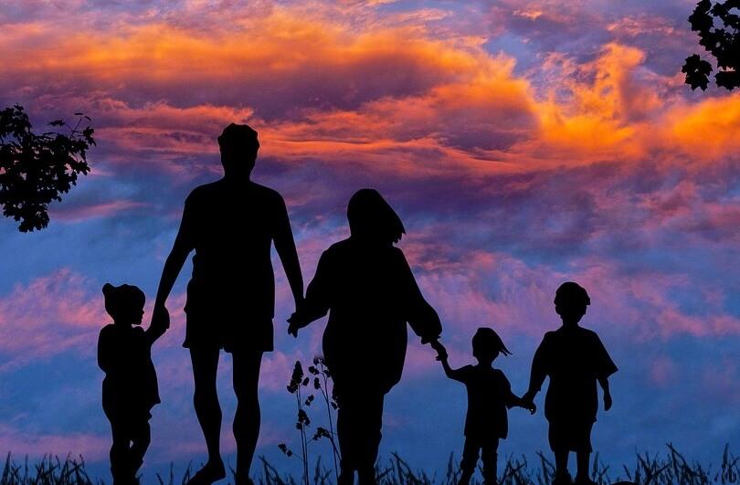 На фото семья, взявшаяся за руки на фоне неба.