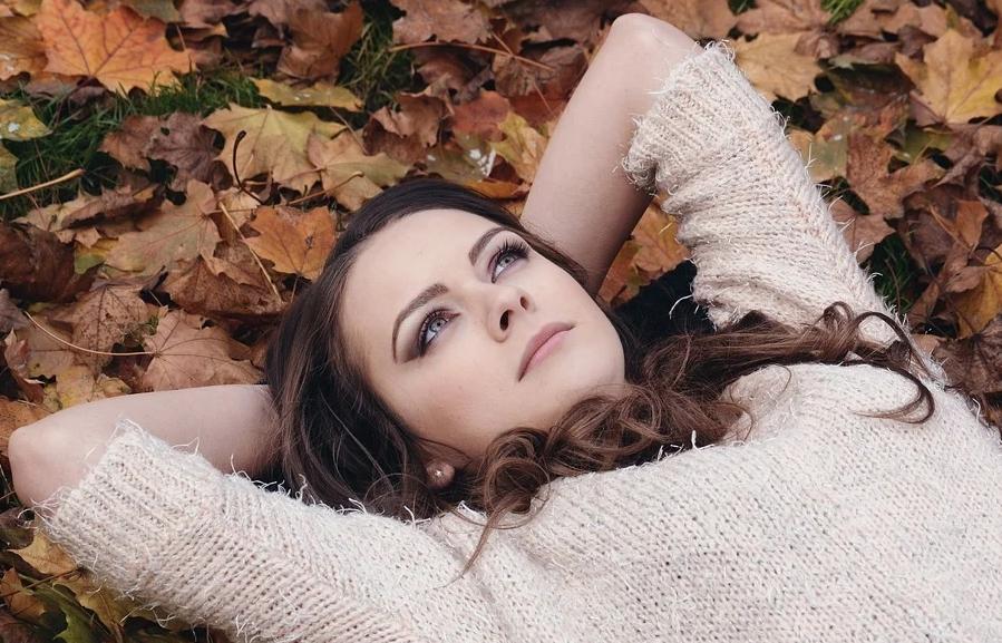 На фото изображена мечтающая девушка.