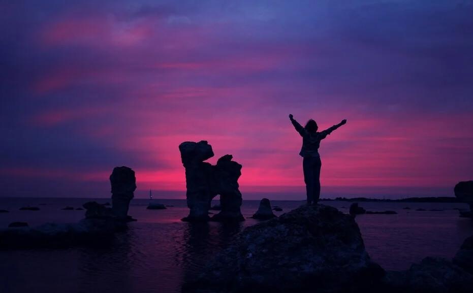 На фото девушка, стоящая на фоне заката.