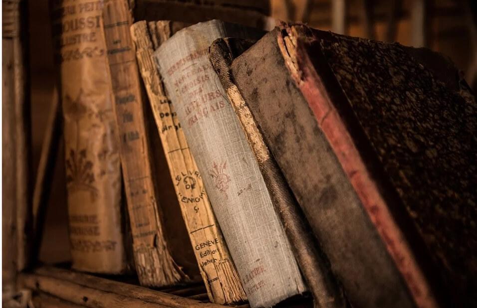 На фото изображены старые книги.