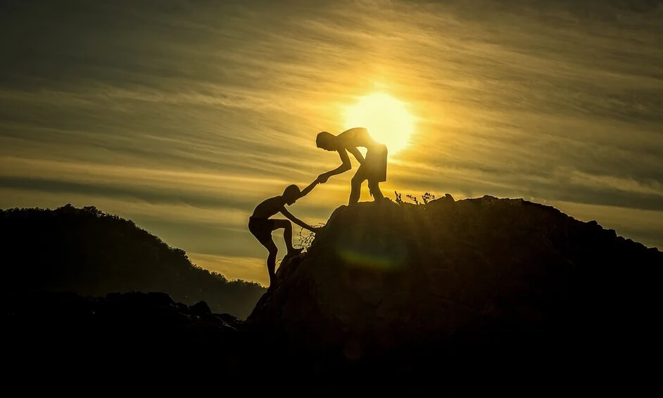 На фото мульчишки взбираются на гору. Один подает руку другому.