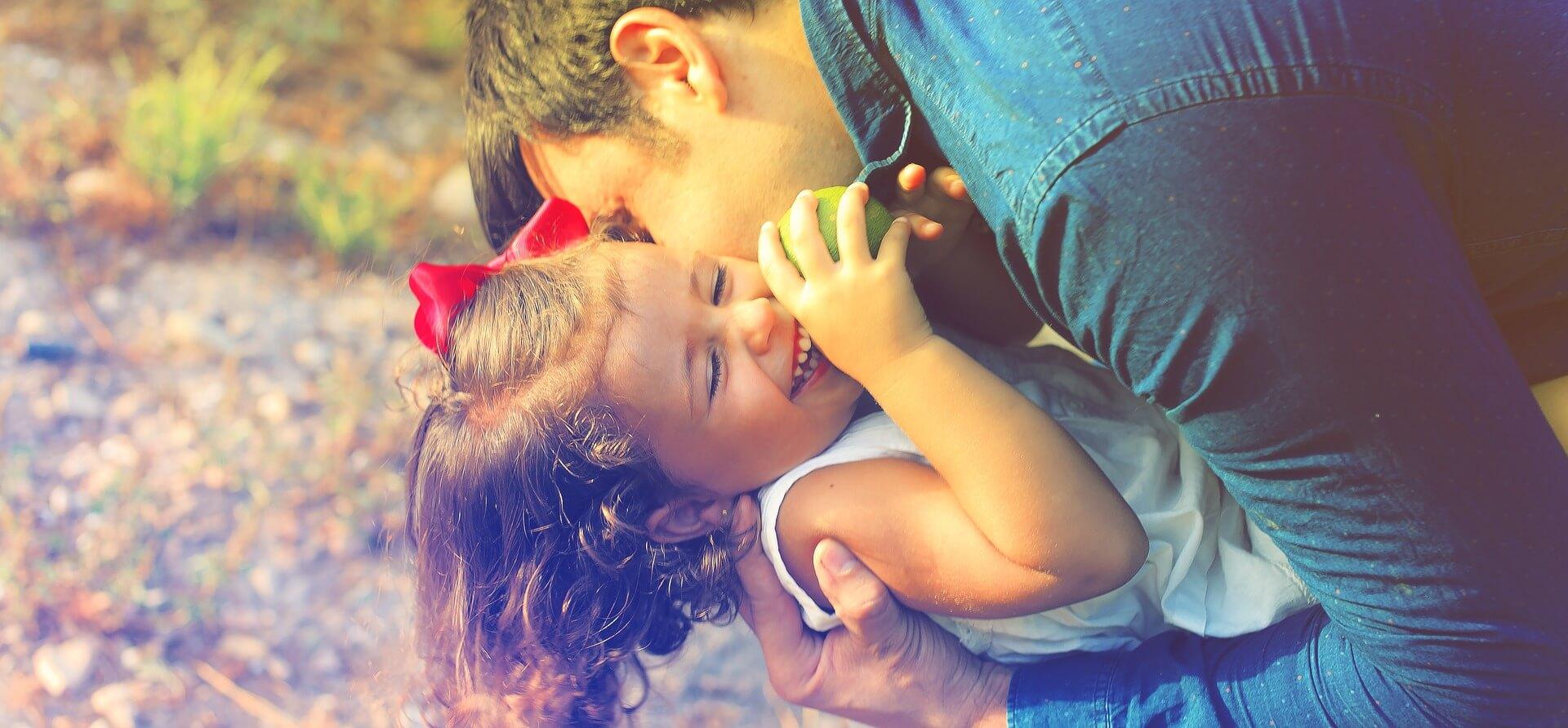Папа обнимает и целует дочку.