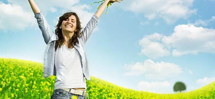 Счастливая девушка в поле с цветами.
