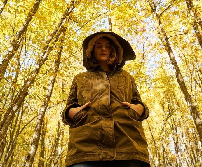 Грустная девушка в осеннем лесу.