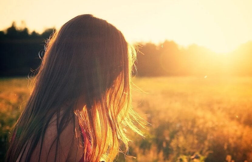 Девушка смотрит на красивый закат.