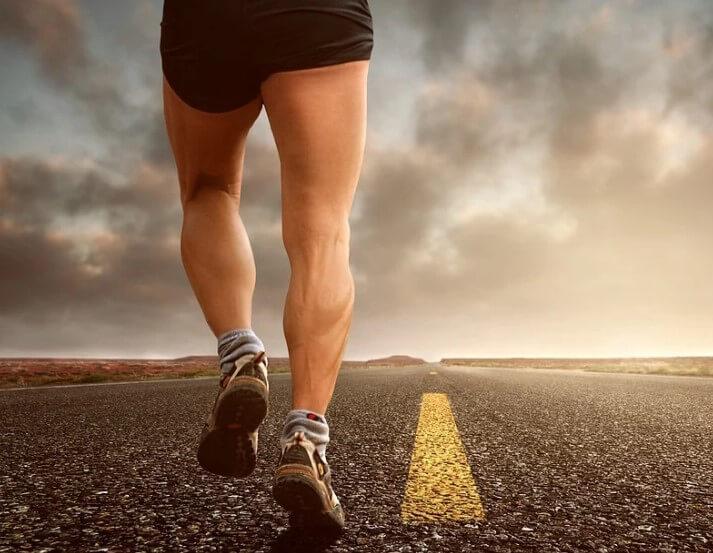 Спортсмен бежит по дороге.