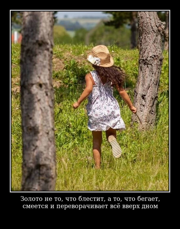 Девочка в платье бежит по саду.