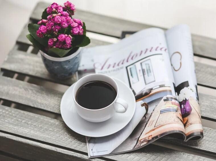 Чашечка кофе, журнал и комнатный цветок.