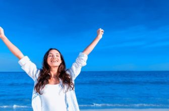 Счастливая девушка на фоне синего моря и голубого неба.