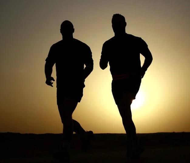 На фото два спортсмена, бегущих на фоне заката.