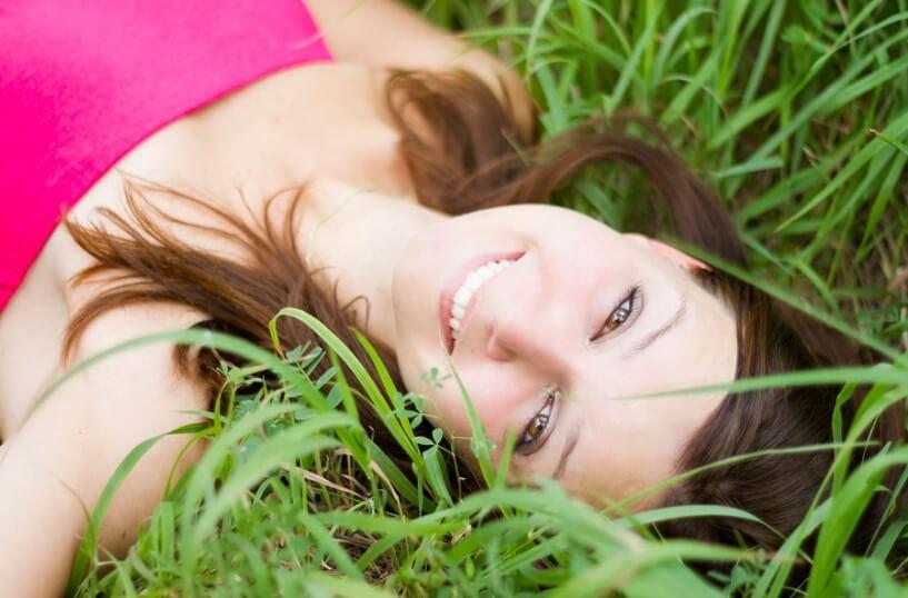 Девушка счастлива. Лежит на траве и улыбается. Красивая улыбка.
