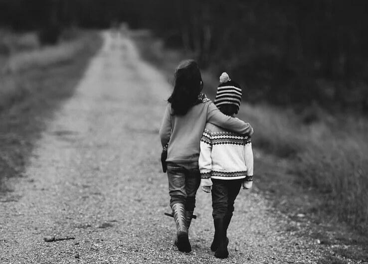 Брат и сестра идут по дороге.