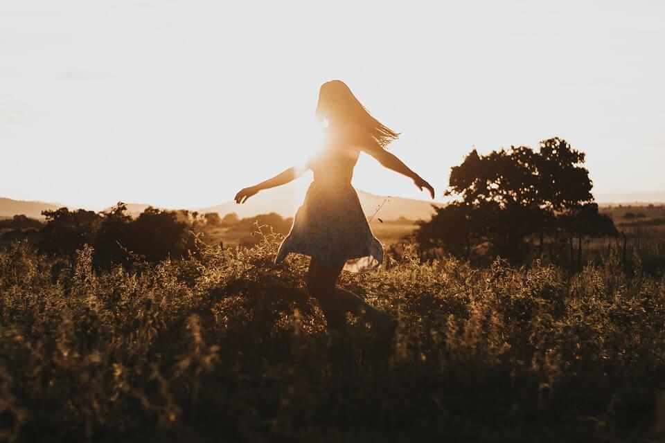 На фото изображена свободная девушка в поле.