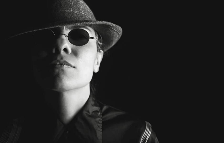 На фото изображена девушка в шляпе, черных очках и мужской рубашке.