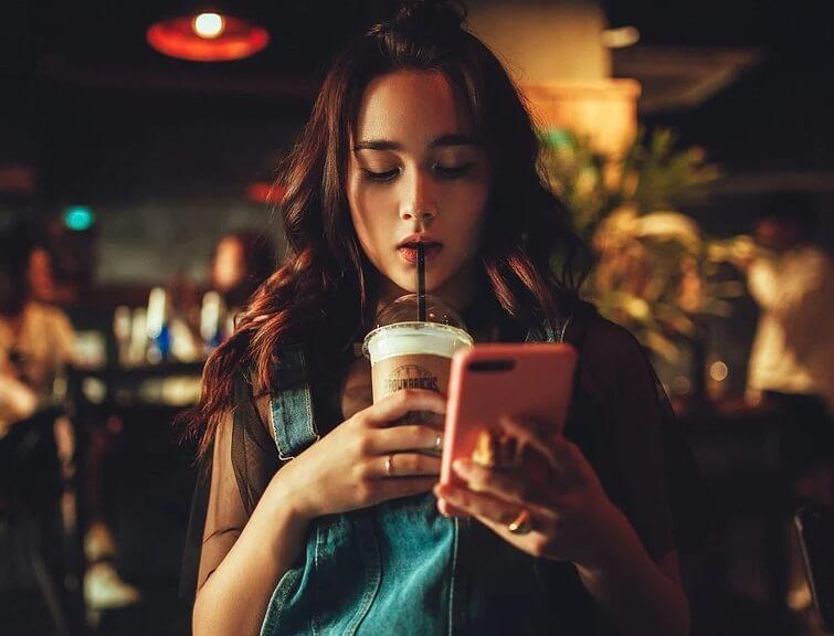 Девушка с телефоном и кофе.