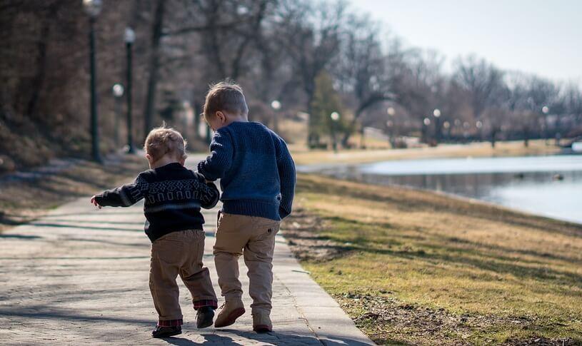 Два брата идут по улице вдоль реки.