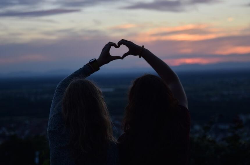 На фото изображены подруги. Сидят и смотрят на закат.