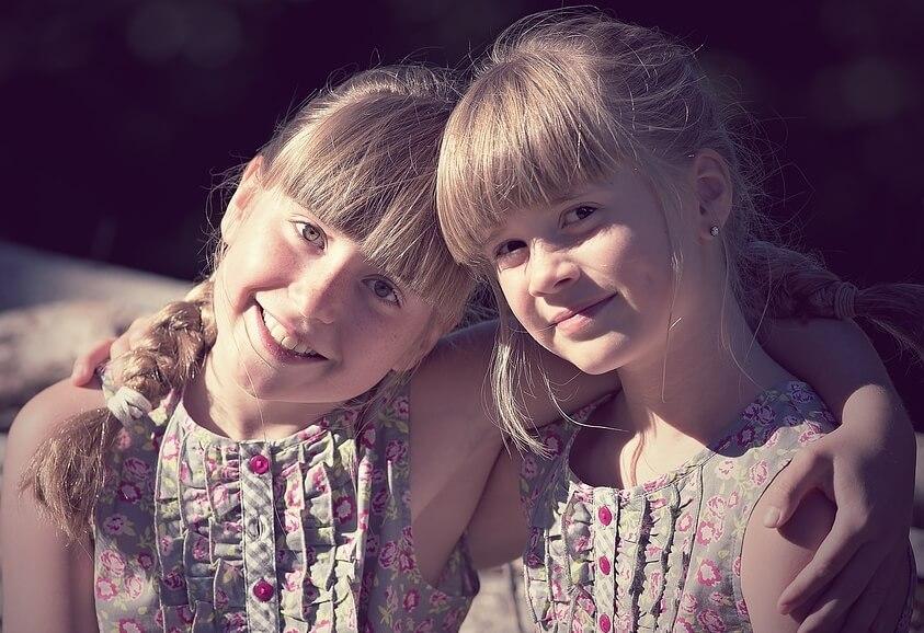 На фото две девочки, которые обнимаются.