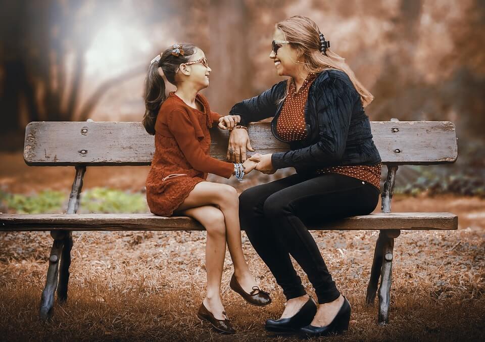 На фото изображены мама и дочь, сидящие на скамейке.