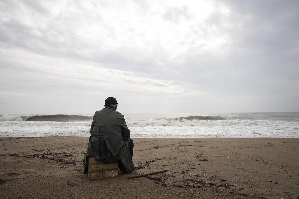 На фото изображен мужчина, который сидит у моря в одиночестве.