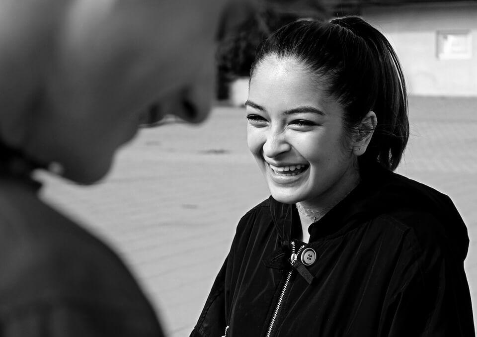 На фото изображена девушка, которая смеется.