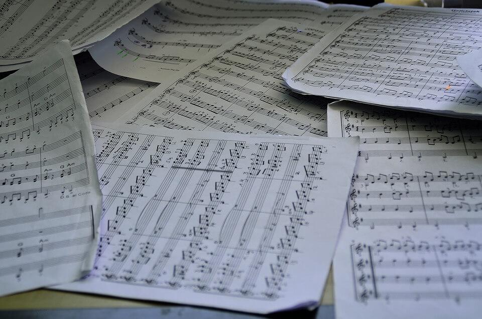 На фото изображены листы с нотами произведений.