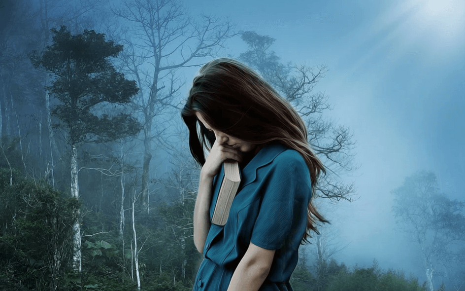 На фото изображена девушка с книгой в руках в туманном лесу.