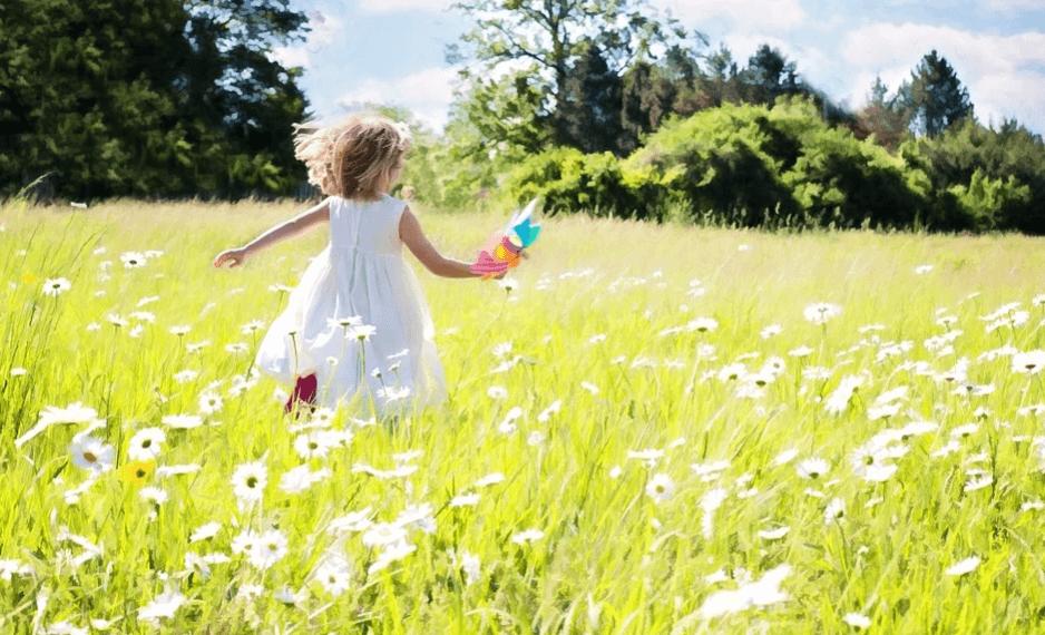 На фото изображена девочка, которая бежит в поле.