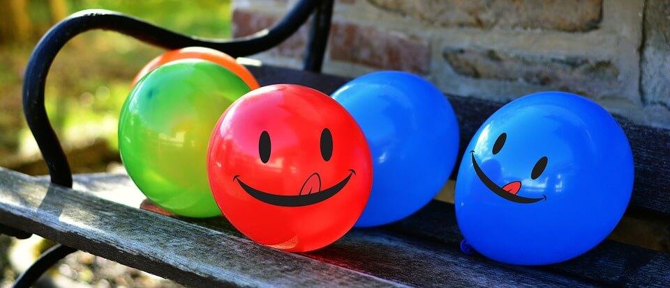 На фото изображены воздушные шары с улыбками на скамейке.