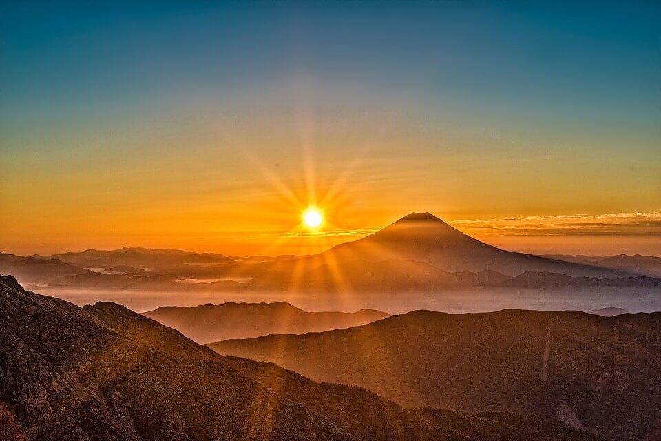 На фото изображено солнце в горах.