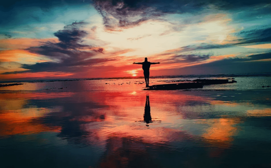 На фото изображен силуэт человека с распростертыми руками на фоне заката.