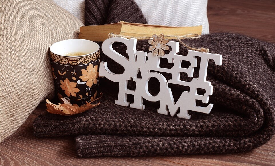На фото изображен плед, чашка кофе, книга и табличка Sweet Home.