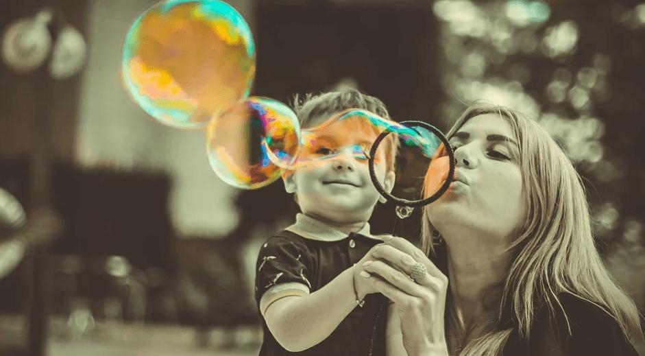 На фото изображены мама с сыном, которые пускают мыльные пузыри.