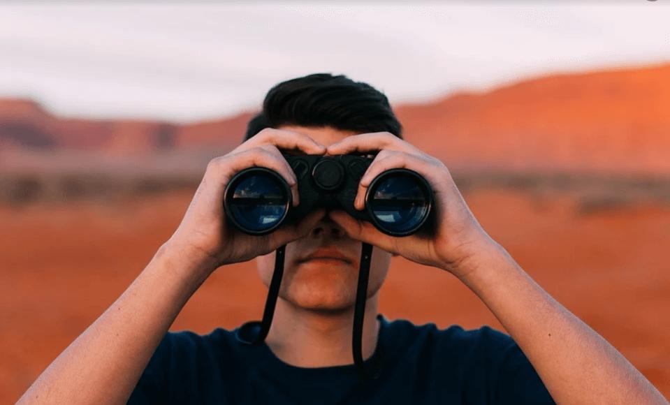 На фото изображен молодой человек, который смотрит в бинокль.