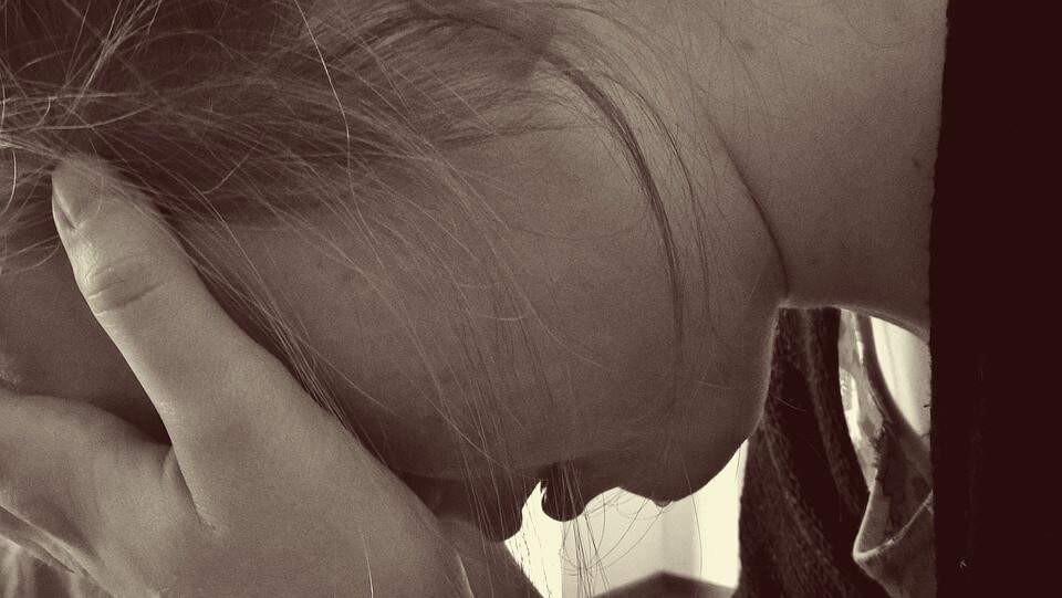 На фото изображена девушка, которая опустила голову и закрыла руками глаза.