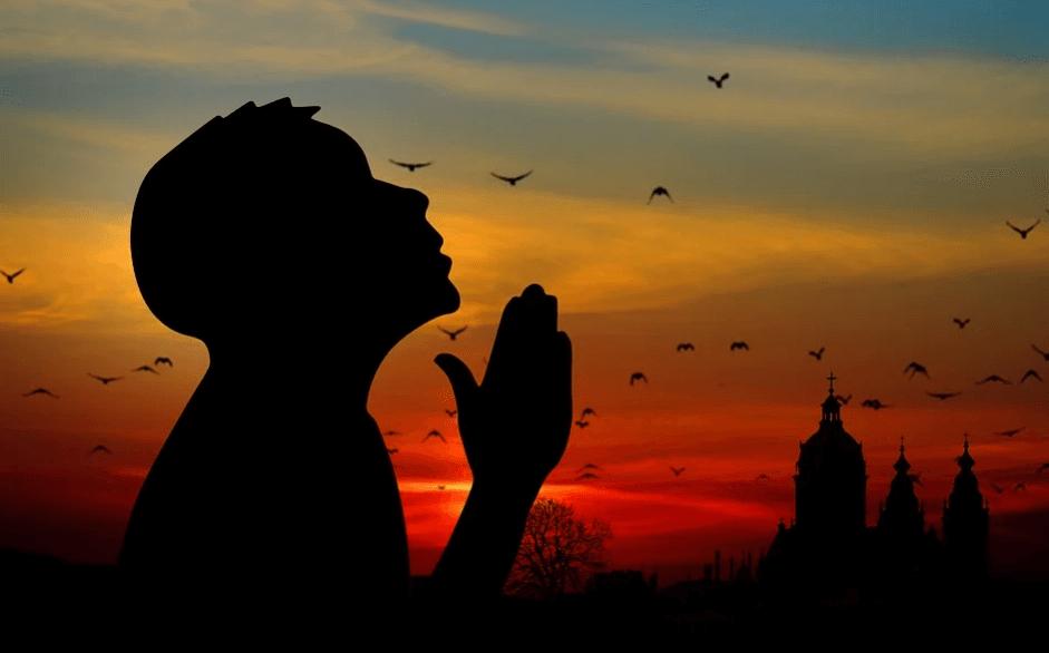 На фото изображен силует человека, который молится.
