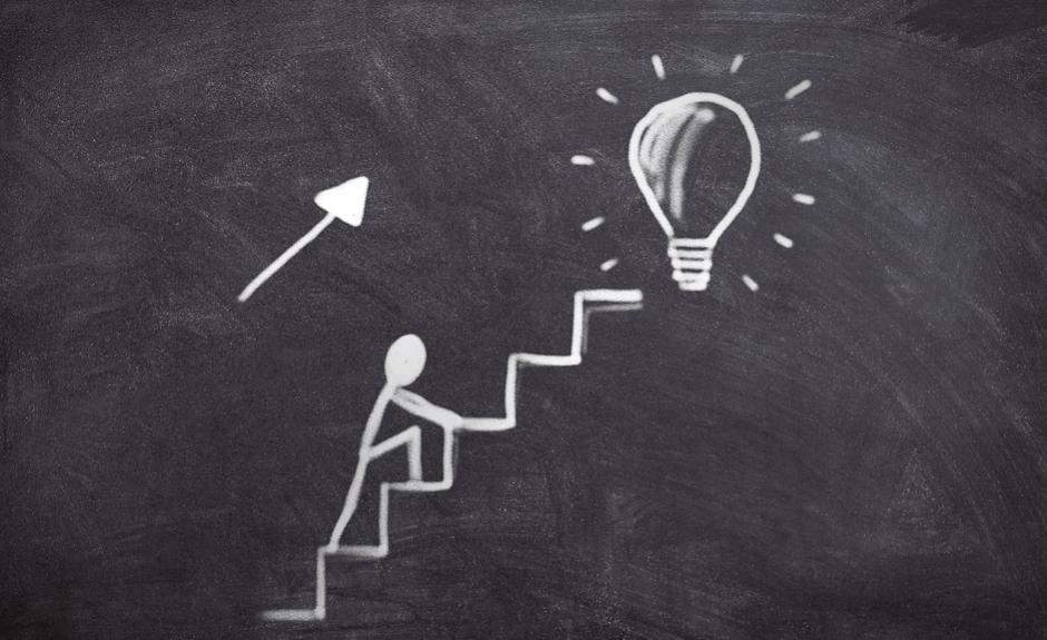 На фото изображен рисунок мелом, где человечек идет по ступеням к цели.