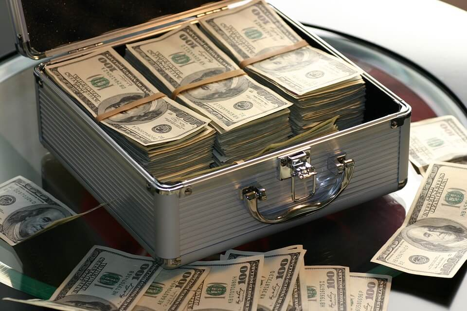 На фото изображен чемоданчик с деньгами.